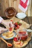 Schmieren der Erdbeermarmelade auf einem Toast zum Frühstück stockbilder
