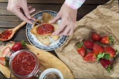 Schmieren der Erdbeermarmelade auf einem Toast zum Frühstück lizenzfreie stockfotos