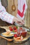 Schmieren der Erdbeermarmelade auf einem Toast zum Frühstück lizenzfreie stockfotografie