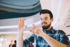 Schmierfilmbildung des jungen Mannes etwas an seinem Handy auf städtischem Hintergrund stockfotos
