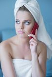Schmollende Frau im Bad-Tuch mit rotem Handy Stockfotografie