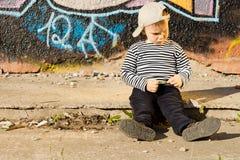 Schmollender kleiner Junge, der auf einem Bürgersteig sitzt Lizenzfreies Stockfoto