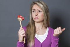 Schmollendes Mädchen 20s mit Tellerbürste bohrte in der Hand am Waschen und am Säubern Stockfotografie