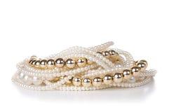 Schmuck gemacht vom Gold und von den weißen Perlen Stockfotografie