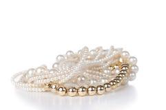 Schmuck gemacht vom Gold und von den weißen Perlen Stockfoto