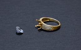 Schmuckarbeit, Goldring mit einem Diamanten, Vorbereitung für die Installierung eines Steins auf einen Ring, dunkler Hintergrund stockbild