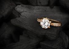 Schmuckring mit großem Diamanten auf dunklem Kohlenhintergrund, weiches foc Stockfotos
