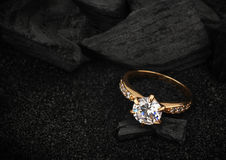 Schmuckring mit großem Diamanten auf dunkler Kohle und schwarzem Sand backg Lizenzfreie Stockfotografie