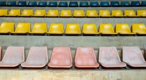 Schmutz-alte multi Farbe Seat in der Stadions-Hintergrund-Beschaffenheit Lizenzfreies Stockfoto