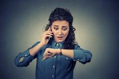 Schmutz-Hintergrund für Ihre Veröffentlichungen Betonte Geschäftsfrau, welche die Armbanduhr, spät laufend betrachtet Stockfoto