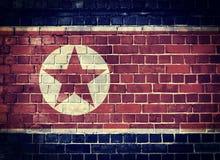 Schmutz-Nordkorea-Flagge auf einer Backsteinmauer Stockbilder