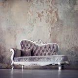 Schmutz redete Innenraum an Schönes Sofa in der klassischen Art auf einem Hintergrund von strukturierten Wänden Stockbild