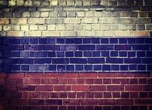 Schmutz-Russland-Flagge auf einer Backsteinmauer Stockfotos