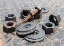 Schmutz-Schrauben-Nuts Bolzen und Ringe auf Diamond Steel Plate Stockbild