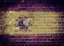 Schmutz-Spanien-Flagge auf einer Backsteinmauer Lizenzfreie Stockfotos