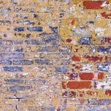 Schmutz verwitterte Backsteinmauerrot mit blauem gelbem und weißem peeli Lizenzfreie Stockfotos