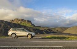 Schmutzig weg von stehender folgender Asphaltstraße des Straßenautos mit Island-Nordsommerlandschaft, grünen Sie abgefressene Ber lizenzfreies stockbild