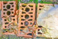 Schmutzige alte gebrochene Ziegelsteine auf dem Boden mit grünem Gras Lizenzfreies Stockfoto