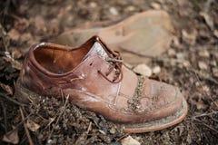 Schmutzige alte Paare Schuhe bedeckt im Boden lizenzfreie stockfotografie