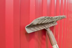 Schmutzige alte Rührstange gegen den roten Zaun Lizenzfreie Stockfotografie