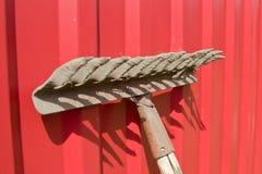 Schmutzige alte Rührstange gegen den roten Zaun Stockfotos