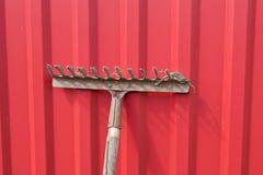 Schmutzige alte Rührstange gegen den roten Zaun Lizenzfreies Stockfoto