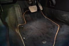 Schmutzige Autofußmatten des schwarzen Teppichs mit Gaspedalen und -bremsen in der Werkstatt für das Schilderungsfahrzeug vor tro stockfotos