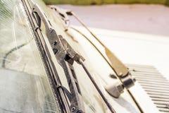 Schmutzige Autowindschutzscheibe mit dem enthaltenen Glasreiniger, in der Großstadtfront und in der Rückseite des Hintergrundes w stockfotografie