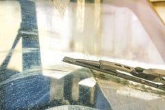 Schmutzige Autowindschutzscheibe mit dem enthaltenen Glasreiniger, in der Großstadtfront und in der Rückseite des Hintergrundes w stockbild