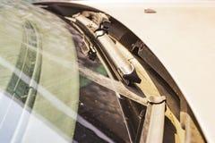 Schmutzige Autowindschutzscheibe mit dem enthaltenen Glasreiniger, in der Großstadtfront und in der Rückseite des Hintergrundes w stockfotos