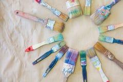 Schmutzige benutzte Künstler ` s Bürste sind ganz herum Hintergrundbeigepapier Stockbilder