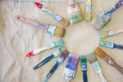 Schmutzige benutzte Künstler ` s Bürste sind ganz herum Hintergrundbeigepapier Lizenzfreie Stockbilder