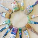 Schmutzige benutzte Künstler ` s Bürste sind ganz herum Hintergrundbeigepapier Stockfotos