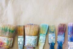 Schmutzige benutzte Künstler ` s Bürsten liegen in Folge oder zeichnen Hintergrund bei Stockfotografie