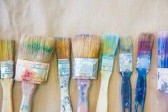 Schmutzige benutzte Künstler ` s Bürsten liegen in Folge oder zeichnen Hintergrund bei Lizenzfreies Stockfoto