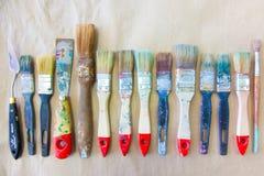 Schmutzige benutzte Künstler ` s Bürsten liegen in Folge oder zeichnen Hintergrund bei Stockfoto