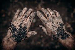Schmutzige Hände des Bergmannes halten Kohle Konzeptindustriebergbau stockfotografie
