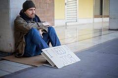 Schmutzige Hände des obdachlosen Whit, die allein trinken Stockbilder