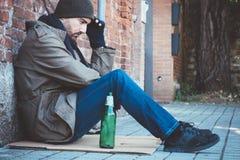 Schmutzige Hände des obdachlosen Whit, die allein trinken Lizenzfreie Stockfotos