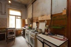 Schmutzige Küche mit Möbeln und Gasherden ist in der Wohnung für vorübergehende lebende Bestehenflüchtlinge, die zu mig gezwungen stockfotos