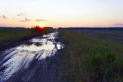 Schmutzige Landstraße unter Feldern bei Sonnenuntergang Stockfotografie