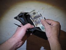 Schmutzige Mannhände halten in meiner Hand eine alte zerschlagene Geldbörse und Geldbeutel einen gebrannten 100-Dollar - Schein a Lizenzfreie Stockfotos