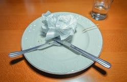 Schmutzige Platte mit Gabel, Messer und benutzter Serviette an Stockfotografie