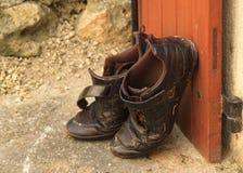 Schmutzige Schuhe außerhalb der Tür lizenzfreie stockbilder