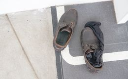 Schmutzige Schuhe und schwarze Socken auf dem Boden im Büro Stockbild
