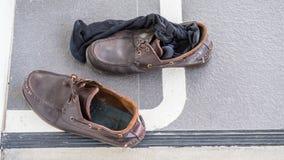 Schmutzige Schuhe und schwarze Socken auf dem Boden im Büro Stockbilder