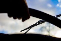 Schmutzige verkratzte Autowindschutzscheibe mit Wischer durch unscharfes Lenkrad mit der Hand des Fahrers auf unscharfem Hintergr lizenzfreie stockbilder