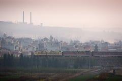 Schmutzige Verschmutzung Ein Zug führt die alte Stadt des Südens Yunnan, China, Land der Kohle Kohlenbergbau mit Rohren auf dem B lizenzfreie stockbilder
