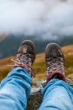 Schmutzige wandernde Schuhe mit Bergen und Wolken im Hintergrund stockfotografie