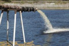 Schmutzige Wasserströme von einem Rohr stockfotografie